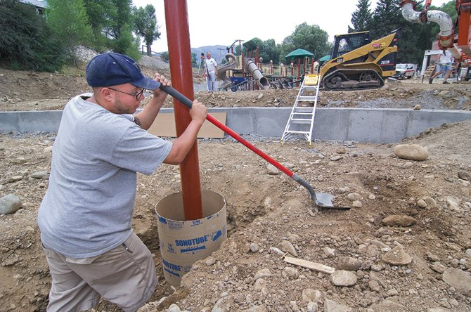 Volunteer Travis McNair fills around a concrete form at the new Soda Creek Elementary School playground Monday morning. Volunteers helped build the new playground, and a new one at Strawberry Park Elementary School last weekend. However, there still were a few details left on Monday and, thankfully, a few volunteers willing to come out and help.