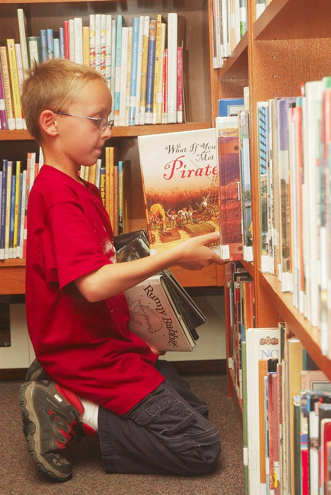 Matai Curzon, who will be a third-grader this fall at Soda Creek Elementary School, checks out a book Tuesday at Bud Werner Memorial Library. Last school year, 85 percent of the third-graders at the school tested proficient or advanced in reading, 15 percentage points above the state average.