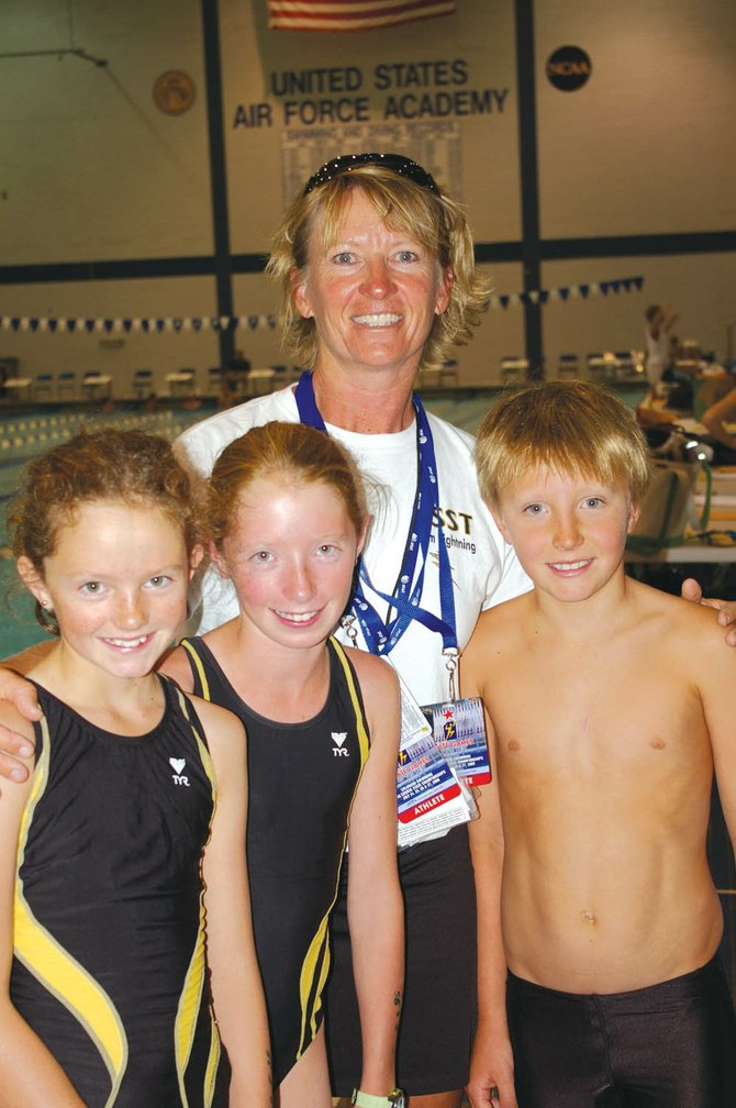 Margaret Lichtenfels, from left, Samantha Terranova, coach Jill Ruppel and Frank Ruppel take a break at the Colorado State Long Course Championships. The meet brought some of the best swimmers from across Colorado to the Air Force Academy.