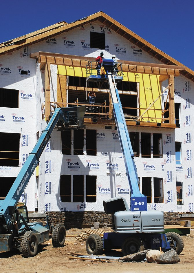 Workers for Custom On-Site Construction install timber beams at Trailhead Lodge on Thursday. Completion of the building in Wildhorse Meadows is a year away. The general contractor is Drahota Construction.