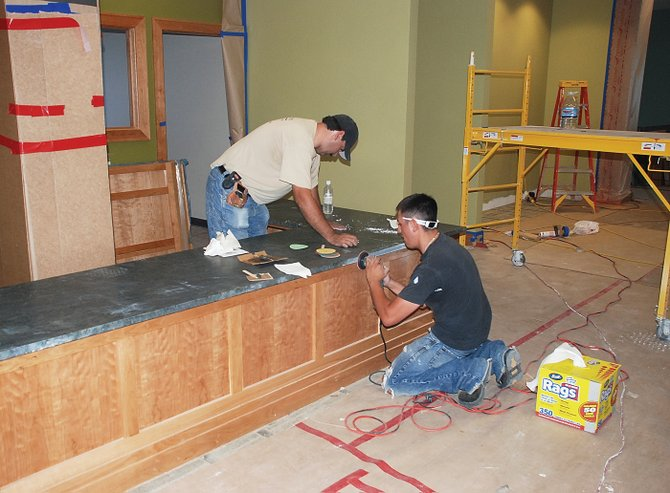 Mike Martinez Jr. and Arturo Pinedo of Stone Concepts in Brighton polish the honed verde San Francisco granite on the new reference desk Friday in the Bud Werner Memorial Library.