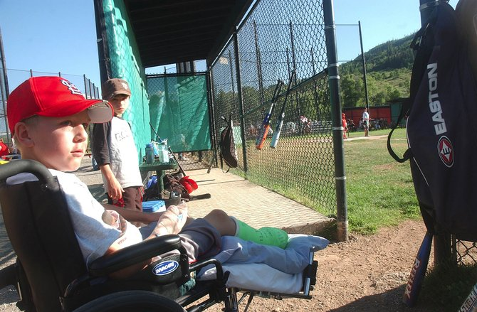 Ten-year-old Tyler Johnson watches his Little League Baseball team Friday with his friend Colton Pasternak at Emerald Park. A fundraiser for Tyler is being held from 2 to 8 p.m. Aug. 23 at the Steamboat Springs Community Center.