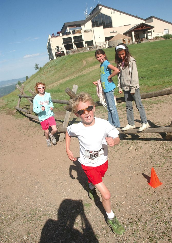 Seven-year-old Tyler Scholl, of Kremmling, passes the finish line of the 5-mile Mount Werner Classic on Saturday morning. Tyler finished the race in fourth place, with a time of 1 hour, 54 seconds.
