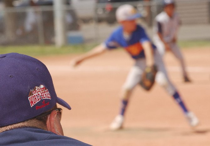 Damien Christian, coach of the So Cal Mizuno Triple Crown Sports baseball team, watches his team face pitcher Joey Collura, of the High Heat team from Glendale, Ariz., on Wednesday at Howelsen Park.