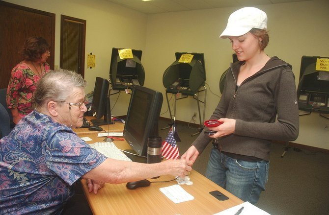 "Election judge Barb De Vries hands Susanna Lockhart an ""I voted"" sticker after voting early in the election primary  Tuesday at the Routt County Courthouse. It was the first time Lockhart has voted. De Vries has been volunteering in Routt County elections for 40 years."