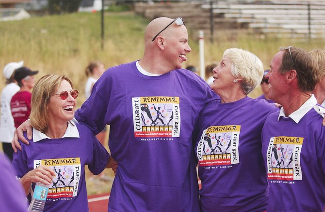 Cancer survivors, from left, Sandy Jenny, Jason Sear, Bev Engel and Keith Leifer participate Friday in the Survivor Walk during the American Cancer Society Relay For Life at the Steamboat Springs High School.