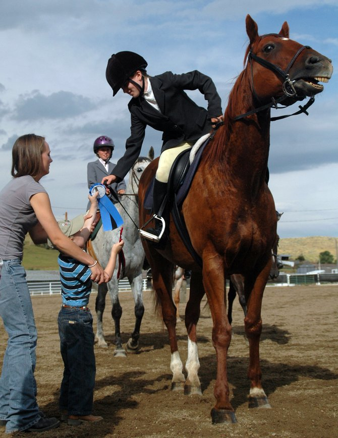 Jordan Sidwell, 4, hands a blue ribbon to Arielle Gold on Friday at the Hunter Under Saddle 11 to 13 English riding competition at the Routt County Fairgrounds in Hayden. Gold won the event atop her horse, Whole Lotta Gone.