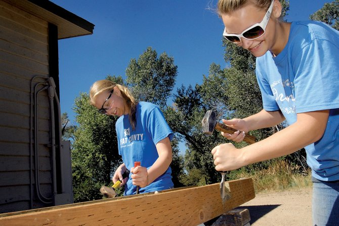 Kirsten McAlexander, left, 16, and Challyn Pfifer, 17, chisel beams Wednesday at Yampa River State Park. The pair are constructing six informational kiosks for their Girl Scout Gold Award Project.