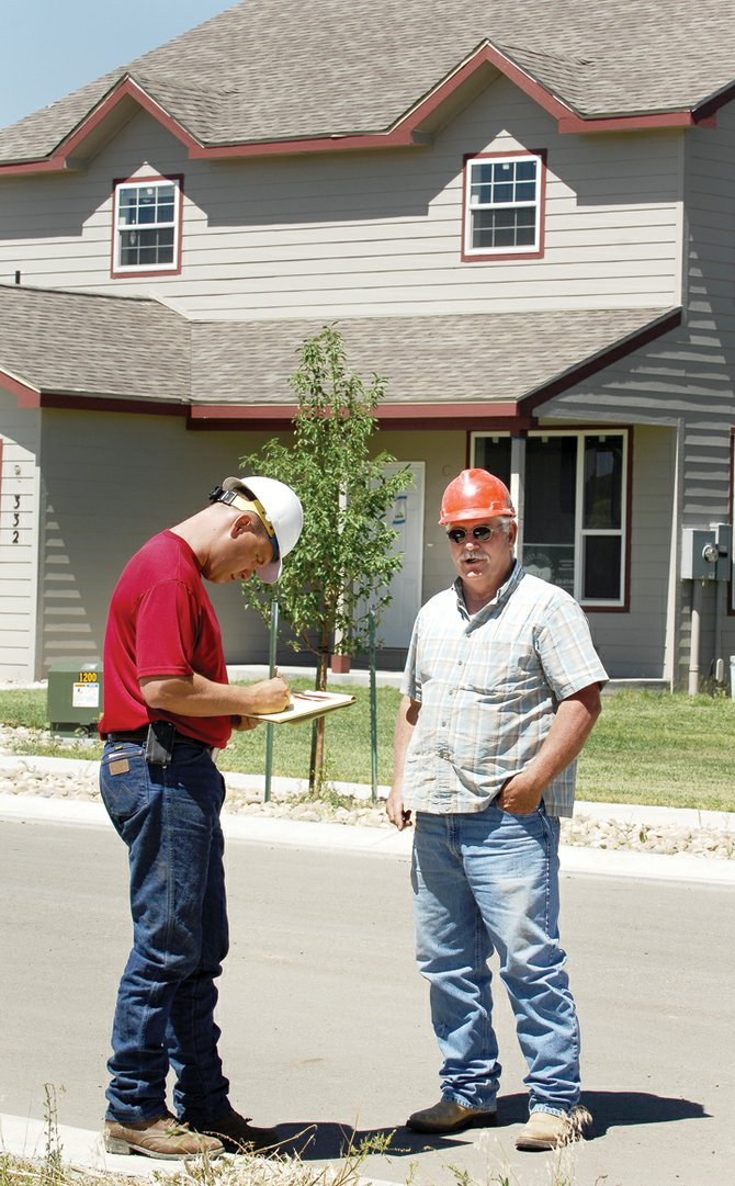 Kirk Moisan, a project executive for Robinson Construction, talks with the owner of a private dump truck company at the Lake Village subdivision.