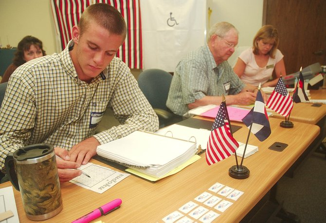 Routt County election officials, from left, Eric Bonner, Bruce Lindahl and Barbara Houston do puzzles to pass the time Tuesday during a slow primary election day. By 3 p.m., five people had voted at the courthouse.