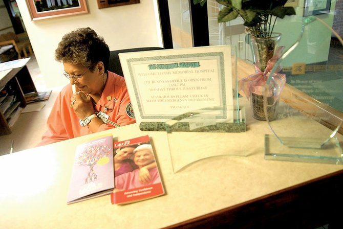 Margarita McKenzie answers phones Thursday at The Memorial Hospital. McKenzie, who has been a volunteer Pink Lady for about three years, is among more than 20 ladies who volunteer at the hospital, working the front desk, in the gift shop and other places.