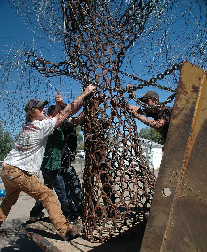 "Isaac Haskins, left, tries to unload ""Rusty Willow,"" his art entry into the Routt County Fair, on Wednesday morning at the fairgrounds in Hayden. Haskins, with the help of friends Chris Skof, Justin Moor, Scott Armbruster and Charley Holmes, used a front loader to get the piece off his truck, then muscled it near the exhibition hall. He said the piece, made of horseshoes and scrap metal from his Hayden welding business, took about 100 hours and a lot of help from friends and family to complete."