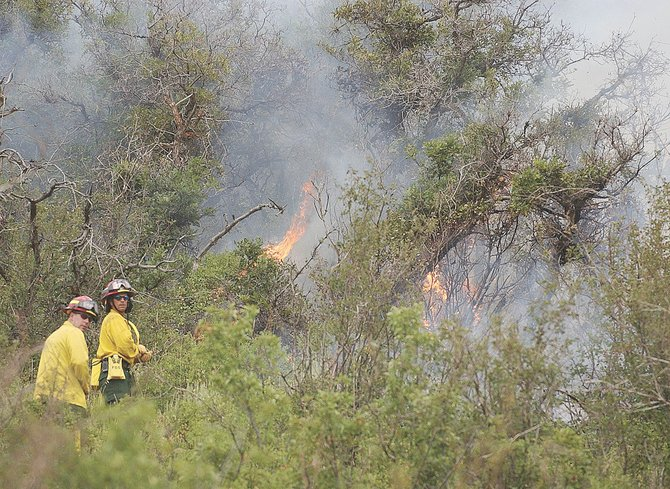 Steamboat Springs firefighters Chris Moore, left, and Dave Meissner climb a hillside toward a wildfire along Routt County Road 41 southwest of Steamboat Springs. The fire threatened two homes but was contained Thursday evening.