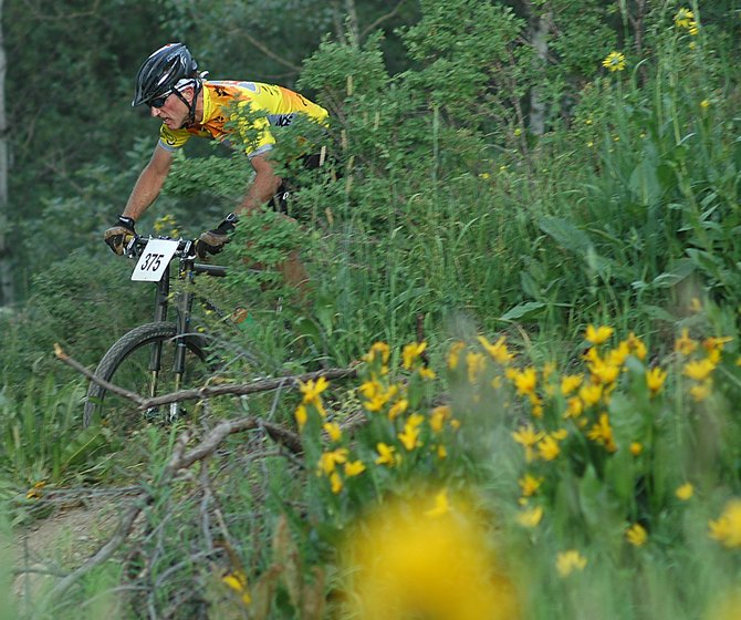 J.P. Pougiales cuts down a trail on Emerald Mountain earlier this summer during a Town Challenge mountain bike race.