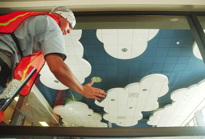 James Demichelis, with Specialty Cleaning Services, cleans a window facing into the entry area at the new Soda Creek Elementary School on Thursday. The ceiling, which was constructed using white and blue ceiling tiles to resemble a sky, is one of the unique features at the school, which is nearing completion.