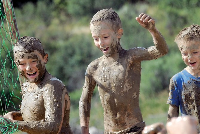 Deven Mosman, 9, left, Cole White, 8, middle, and Seth White, 5, cheer on players Saturday at the ninth annual Mud Splash mud volleyball tournament at Loudy-Simpson Park. The event, a fundraiser for the Craig Chamber of Commerce, pitted teams against one another in a double-elimination tournament.