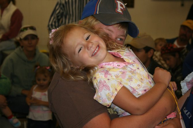 Madison Thomas, 3, is tickled by her cousin, Lane Moon, on Sunday at the Routt County Fair in Hayden. Moon was trying to make Madison laugh during the fair&#39;s Pretty Baby Contest. The tickling paid off, as Madison took the award for best female smile. 