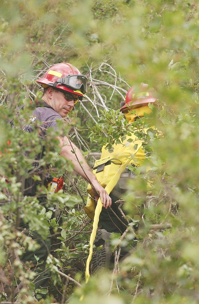 Steamboat Springs firefighters Chris Moore, left, and Dave Meissner, hike Thursday through thick shrub oak toward a wildland fire along Routt County Road 41 southwest of Steamboat Springs.