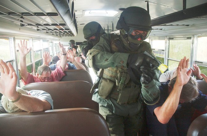 Routt County Sheriff's Office Sgt. Seth Merrick leads a SWAT team through a school bus Wednesday during a training exercise at the Routt County Rifle Club range. The exercise involved school bus drivers and school officials from throughout Routt County.