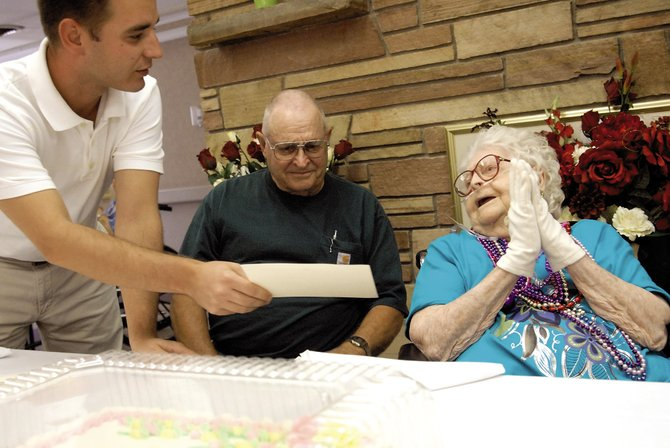 Jonathan Marks, Sandrock Ridge Care & Rehab Administrative Director, presents Hilda Schmidt with a letter Thursday signed by President George Bush and First Lady Laura Bush congratulating her on her 100th birthday. Sandrock Ridge residents gathered together to celebrate her birthday.
