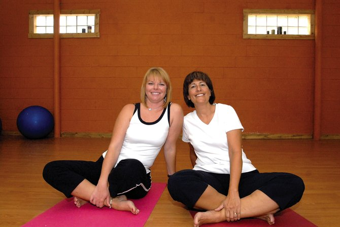 Stephanie Perez, left, certified Pilates trainer, and her student, Deb Bergmann, pause together on their mats Thursday morning at Holistic Health & Fitness. Bergmann is one of about 10 people who started doing Pilates with Perez more than six years ago.