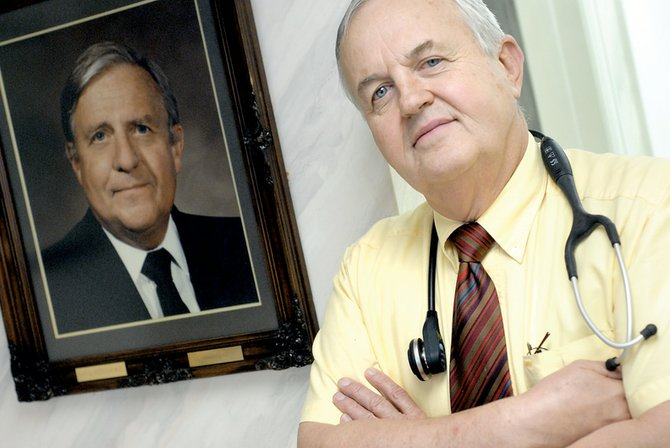 Dr. Thomas Told stands near a framed photograph of his mentor, the late Dr. Ray G. Witham, at Craig Medical Center. Told said he continues to be shaped by Witham, particularly in his belief that immortality lies in passing knowledge onto others. Told, who will receive a prestigious state award tonight in Wyoming, intends to follow his mentor's advice by retiring from the Medical Center in December to become the dean of clinical medicine at Rocky Vista Medical School in Parker, where he will tutor young rural physicians.