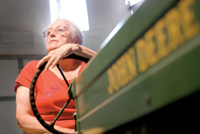 Wilma Willems sits on a John Deere M tractor Thursday in her late husband's shop at their home in Craig. Mike Willems rebuilt the tractor before he died, and it was one of many he worked on throughout the years. Mike recently was honored with the publication of his antique tractor photos in the calendar Old Iron.