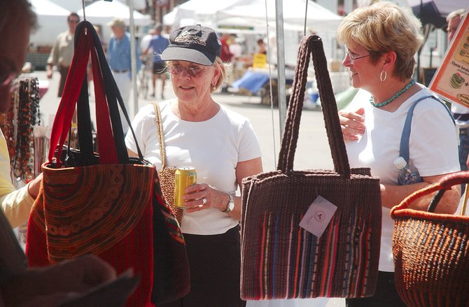 Kathie Cummins, left, and Darlene Swain, of Fort Worth, Texas, check out bags for sale Saturday at the farmers market.
