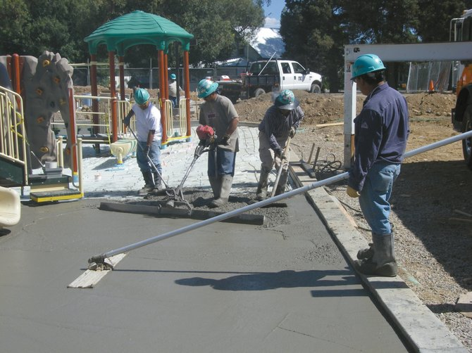 Volunteers from The Industrial Co. and a local carpentry class finish concrete work Thursday at Soda Creek Elementary School's new universal playground. The Education Fund Board, funded by a citywide half-cent sales tax, contributed $250,000 to help build new playgrounds at Soda Creek and Strawberry Park Elementary schools.