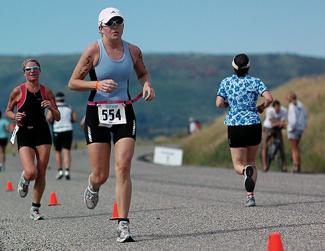 Harmony Zeller, of Centennial, races down the last stretch of the Steamboat Springs Triathlon's four-mile run south of Steamboat as other racers head out after the 20-mile bike race portion of the event Sunday. The race, which takes runners around Lake Catamount, attracted more than 600 competitors.