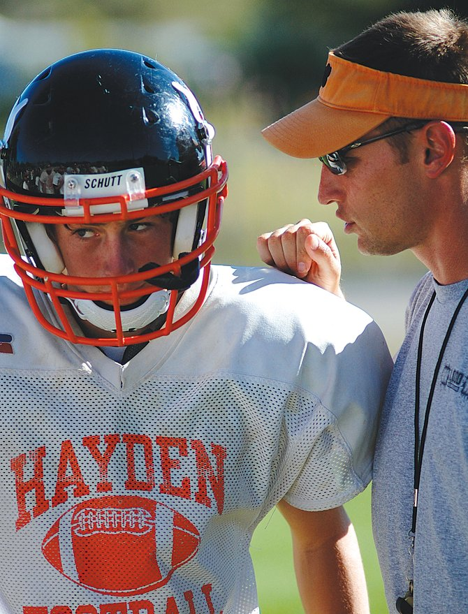 Hayden football coach Shawn Baumgartner, last season's Class 1A coach of the year, relays instructions to sophomore quarterback Graig Medvesk last week during a practice in Hayden. The Tigers open their season at 7 p.m. Friday against Coal Ridge in New Castle.