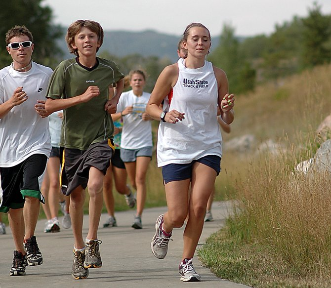 Sophomore Sean Geisler, from left, freshman Asher Rohde and senior Brittany Long run down the Yampa River Core Trail on Wednesday in Steamboat Springs during cross-country practice. The squad's season gets under way next week.