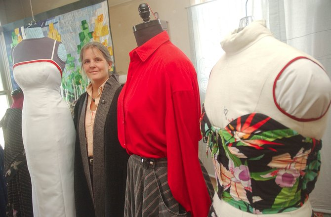 Dressmaker Gale Loveitt stands Wednesday with a few of her custom dresses at her showroom above Lyon&#39;s Corner Drug. 