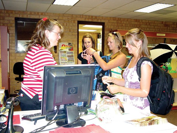 Colorado Northwestern Community College Bookstore Manager Chris Herrera helps a group of dental hygiene students with their book purchases Monday.