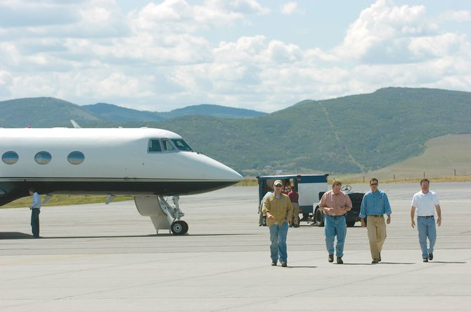 Roy Buchler, from right, John Charpentier, Phillip Myers and Beau Bisso head toward the Spectrum Jet Center in Hayden on Tuesday after returning from a hunting trip in the Northwest Territories of Canada.