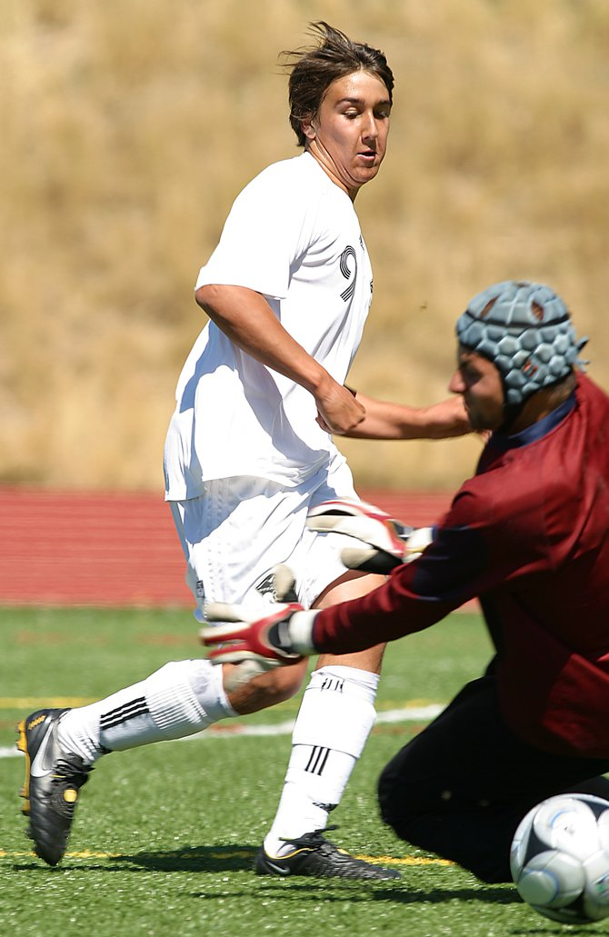 Steamboat senior Daniel Wright slips the ball beneath Vail Mountain School goalie Sean Minett on Saturday in Steamboat Springs. Wright's goal, his second of the game, tied the score at 2. Steamboat later took the lead and won the game, 3-2.