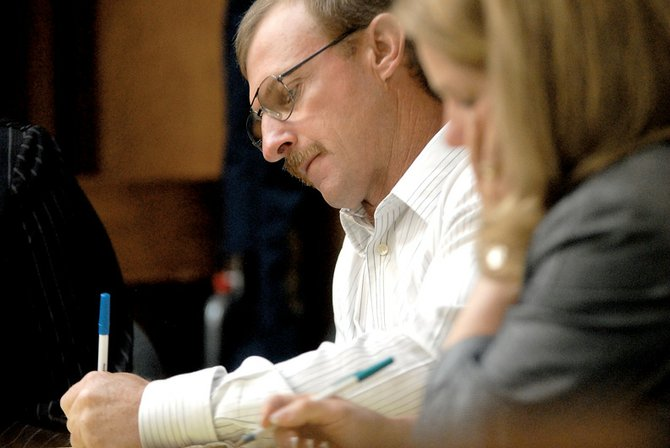 Rodney Culverwell, left, and his defense attorney, Pamela Mackey, take notes Thursday morning during testimony presented by Colorado Division of Wildlife officials appearing for the prosecution. The trial resumes today in Moffat County District Court. Prosecutors said they could rest their case this afternoon.
