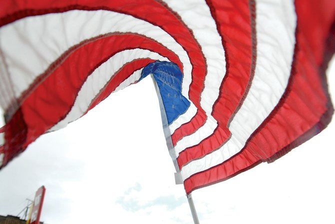 An American flag swirls in the afternoon wind on Labor Day in downtown Craig. The Craig Rotary Club placed the flags.