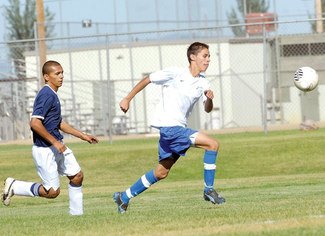 Moffat County High School's Tracy Mendoza blows past a Rifle defender on his way to scoring the team's first goal of the season Tuesday. Mendoza and the Bulldogs couldn't put together another score in a 3-1 loss in the season opener.