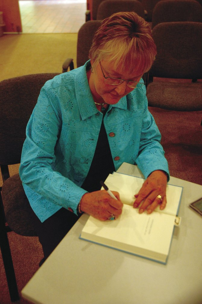 "Julie Jones-Eddy signs a copy of her book, ""Homesteading Women: An oral history of Colorado, 1890 to 1950"" on Saturday afternoon at Craig City Hall. Jones-Eddy gave a presentation Saturday at Craig City Hall about the homesteading women of Northwest Colorado."