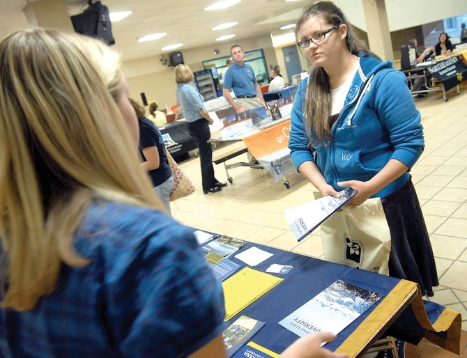 Moffat County High School senior Bonnie Flanders, right, speaks with Kelsy Traeger, admissions representative for Montana State University, on Tuesday at a college fair hosted by Moffat County High School. More than 30 colleges were represented at the fair.