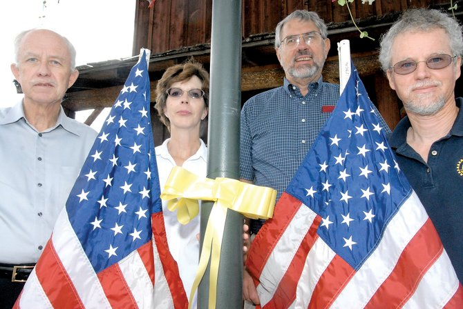Craig Rotary Club members, from left, Bob Johnson, Valerie Rohrich, President Mike Toczek and Randy Looper stand with one of the ribbons Rohrich placed on light poles in the 400 and 500 blocks of Yampa Avenue in recognition of Sept. 11, 2001. The Rotary Club also will be placing flags Thursday along Victory Way and Yampa Avenue to commemorate 9/11.