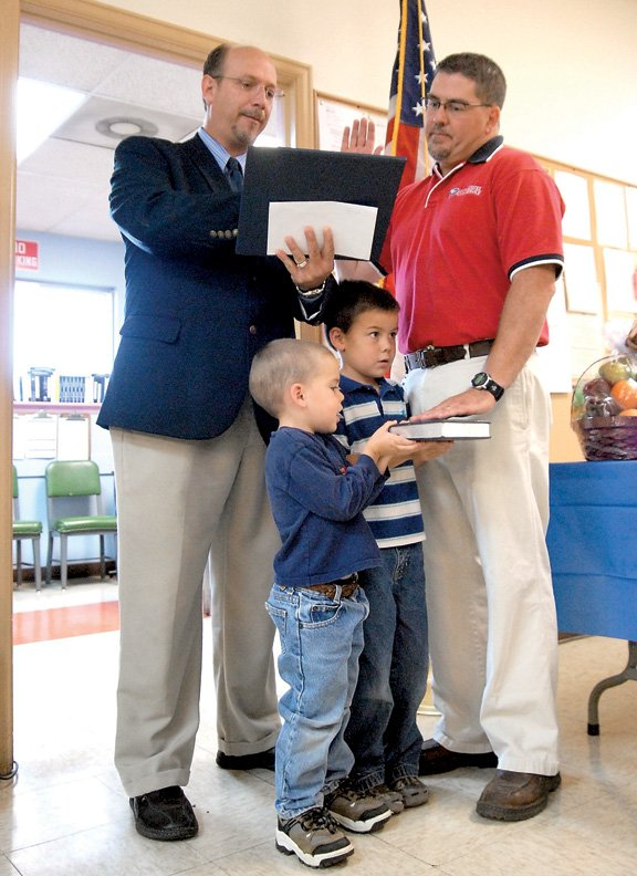 Victor Cordes, right, is sworn into the Craig postmaster position by Area 4 Post Office Operations Manager Mark Lambert on Wednesday with his sons Ryan, 4, left, and Zane, 6, holding the Bible.