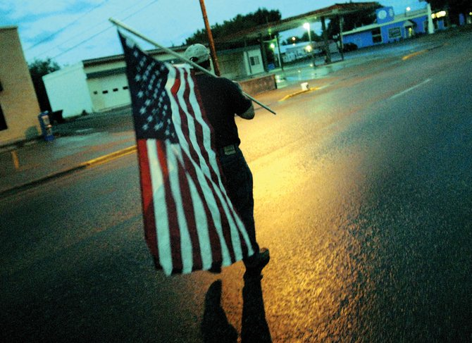 Len Browning walks with a flag Victory Way early Thursday morning. Browning was among 12 Rotary Club members who placed flags along Victory and Yampa Avenue in remembrance of Sept. 11, 2001.