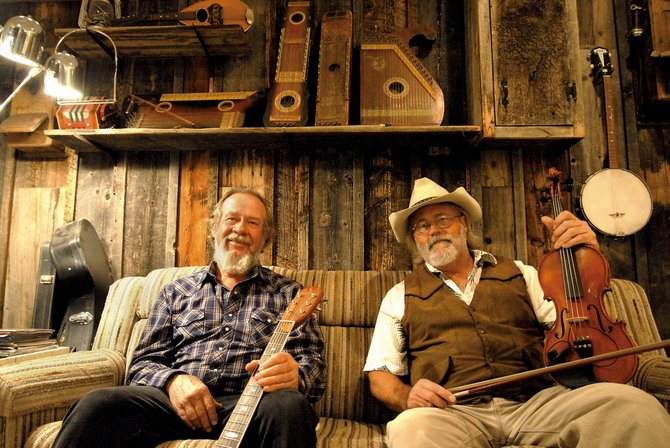 John Allen, left, and Wayne Davis make up the John Wayne Band. They sit in the basement of Allen's home, where the two recorded their first CD.