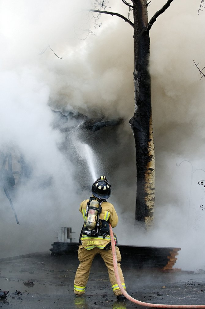 Firefighter Chuck Cerasoli battles a blaze as smoke billows from the garage of a home in the 40500 block of Steamboat Drive, in Steamboat II on Sept. 10. The house and garage were nearly engulfed when crews from Steamboat Springs Fire Rescue arrived, Assistant Fire Chief Bob Struble said. No injuries occurred in the blaze.