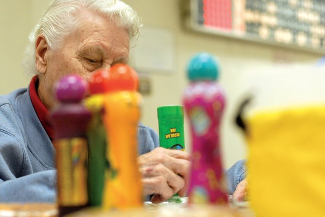 "Ruby Wooden marks her card in a game of ""Blackout"" during Bingo on a Friday night in February at the Elks Lodge. Wooden, who is 88, keeps everything in a precise order - something she's learned to do in the 30 years she estimated she has played. Doors open at 5 tonight for Bingo."