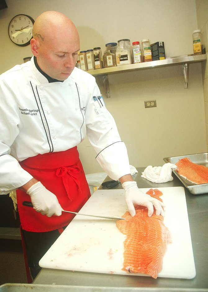 Max Huppert, director of nutritional services for the Steamboat Springs School District, fillets fresh salmon for student lunches last week at Steamboat Springs High School.