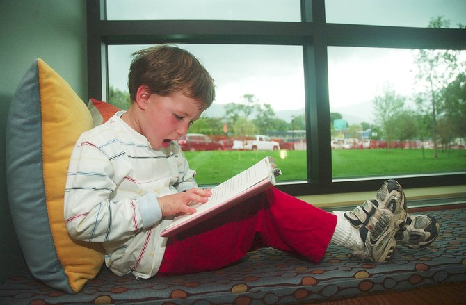 J.J. Macchia, 5, practices his reading in a bay window at the newly expanded Bud Werner Memorial Library, which opened its doors to the public Friday.