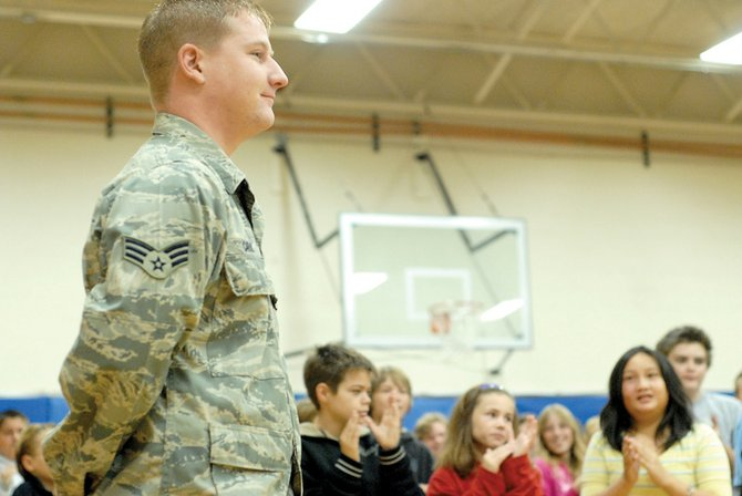 "E.J. Caras, U.S. Air Force senior airman, stands as Craig Intermediate School students applaud his service in Iraq. ""I never got a standing ovation"" before, he said afterward. ""It's pretty cool."""